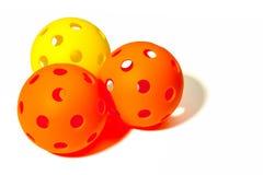 Três Pickleballs - 2 alaranjados e 1 amarelo junto em um fundo branco Imagem de Stock Royalty Free