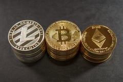Três pilhas de moedas do cryptocurrency Bitcoin, litecoin e ethereum Fotos de Stock