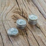 Três pilhas de moedas na tabela de madeira Fotografia de Stock