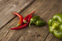 Três pimentas de pimentão encarnados com pimentas verdes Fotos de Stock