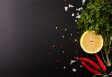 Três pimentas de pimentão vermelho, manjericões, sais grossos e limões em um giz Fotografia de Stock