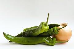Três pimentas e uma cebola Fotos de Stock