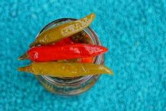 Três pimentas enlatadas pequenas afiadas em um frasco de vidro em um fundo azul Fotografia de Stock