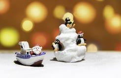 Três pinguins na montanha do gelo com a Santa no barco fotos de stock royalty free
