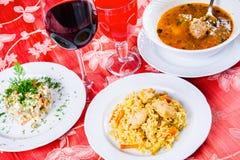 Três placas com os pratos do almoço na tabela Salada, sopa com almôndegas e pilau Fotografia de Stock