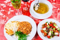 Três placas com os pratos do almoço na tabela A salada, a sopa dos peixes e a costeleta de carneiro vegetais da galinha com solet Imagem de Stock Royalty Free
