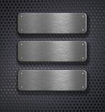 Três placas de metal sobre o fundo da grade Foto de Stock