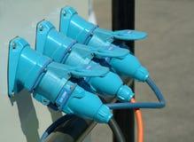 Três plugues de potência azuis conectados Fotografia de Stock