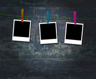 Três Polaroids em branco que penduram em uma linha de roupa Imagem de Stock