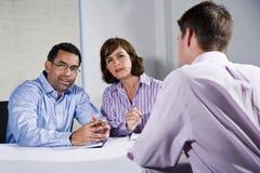 Três povos do meados de-adulto que sentam-se na reunião da tabela imagens de stock royalty free