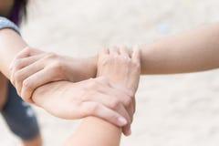 Três povos juntam-se às mãos junto no fundo branco da praia da areia Fotografia de Stock Royalty Free