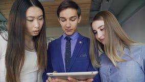 Três povos no negócio attire a vista de uma tabuleta que mantenha um homem vídeos de arquivo