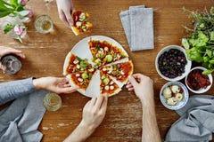 Três povos que compartilham da pizza deliciosa orgânica no partido de jantar fotografia de stock royalty free