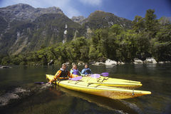 Três povos que Kayaking no lago mountain foto de stock royalty free
