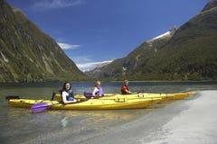 Três povos que Kayaking no lago mountain fotos de stock royalty free