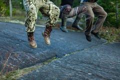 Três povos que saltam em uma rocha imagens de stock royalty free