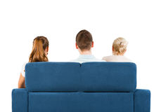 Três povos que sentam-se em um sofá para trás Imagem de Stock