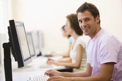 Três povos que sentam-se na dactilografia do quarto de computador Foto de Stock