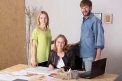 Três povos que trabalham junto imagem de stock
