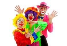 Três povos vestidos acima como dos palhaços engraçados coloridos Imagens de Stock Royalty Free