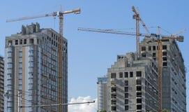 Três prédios e guindastes contra o céu imagens de stock royalty free