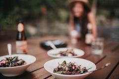 Três pratos da salada em uma tabela, com uma menina no fundo Imagens de Stock Royalty Free
