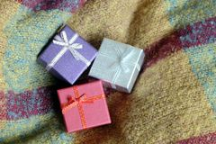 Três presentes de época natalícia em umas caixas coloridas pequenas, cobertas com a fita, contra um fundo do pano de lã Imagens de Stock Royalty Free
