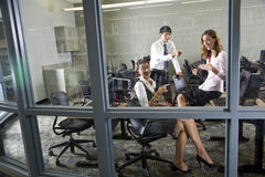 Três professores que encontram-se no quarto de computador da biblioteca Imagens de Stock Royalty Free