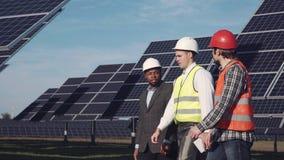 Três profissionais na central elétrica de energias solares Fotos de Stock Royalty Free