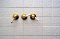 Três punhos dourados da válvula de chuveiro fotografia de stock