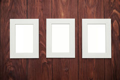 Três quadros vazios no meio na mesa de madeira marrom Imagens de Stock
