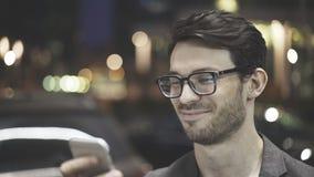 Três quartos de perfil de um homem de sorriso que texting na rua Fotografia de Stock Royalty Free