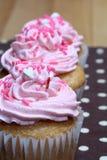 Três queques com crosta de gelo cor-de-rosa e polvilham Fotografia de Stock Royalty Free