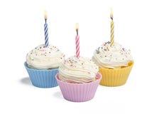 Três queques com vela Imagem de Stock Royalty Free