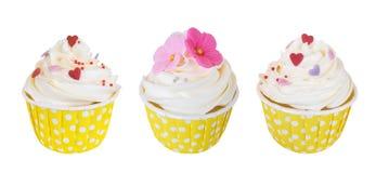 Três queques de creme da manteiga com flores doces e corações no copo de papel do às bolinhas isolado no fundo branco, trajeto Fotografia de Stock Royalty Free