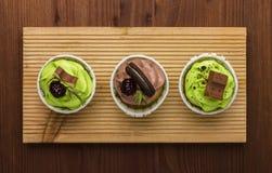 Três queques em uma placa de madeira Fundo de madeira Uma sobremesa deliciosa Fotografia de Stock Royalty Free