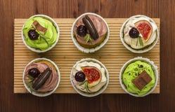 Três queques em uma placa de madeira Fundo de madeira Uma sobremesa deliciosa Imagem de Stock Royalty Free