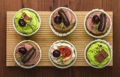 Três queques em uma placa de madeira Fundo de madeira Uma sobremesa deliciosa Fotos de Stock Royalty Free