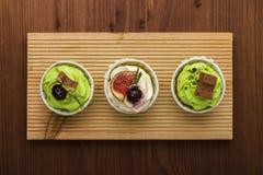 Três queques em uma placa de madeira Fundo de madeira Uma sobremesa deliciosa Fotos de Stock