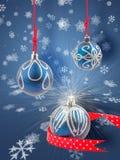Três quinquilharias do Natal com fundo dos flocos de neve Fotografia de Stock Royalty Free