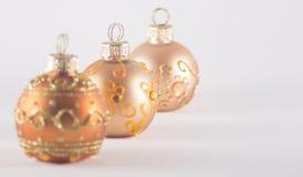 Três quinquilharias do Natal do ouro Imagens de Stock Royalty Free