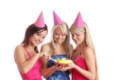 Três raparigas comemoram uma festa de anos imagens de stock