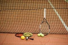 Três raquetes e bolas de tênis na corte interna imagem de stock
