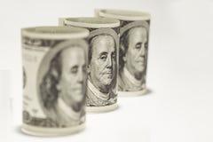 Três rolaram acima de cem notas de dólar em um fundo branco Fotografia de Stock Royalty Free