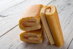 Três rolos doces do sabor da morango na madeira Imagens de Stock