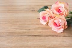 Três rosas cor-de-rosa no fundo de madeira de Brown fotos de stock royalty free