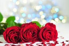 Três rosas entre corações pequenos no fundo das luzes Fotografia de Stock Royalty Free