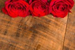 Três rosas vermelhas brilhantes na tabela Fotos de Stock Royalty Free