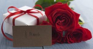 Três rosas vermelhas com caixa de presente e cartão de papel com frase do 8 de março na tabela de madeira azul Foto de Stock Royalty Free