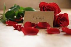 Três rosas vermelhas e pétalas na tabela de madeira velha com o cartão de papel do 8 de março Fotografia de Stock Royalty Free